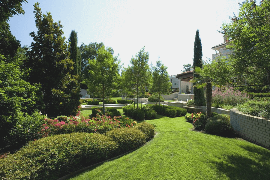 landscaped back yard with flowers, shrubs, and trees that was designed and installed by Lawn Connections