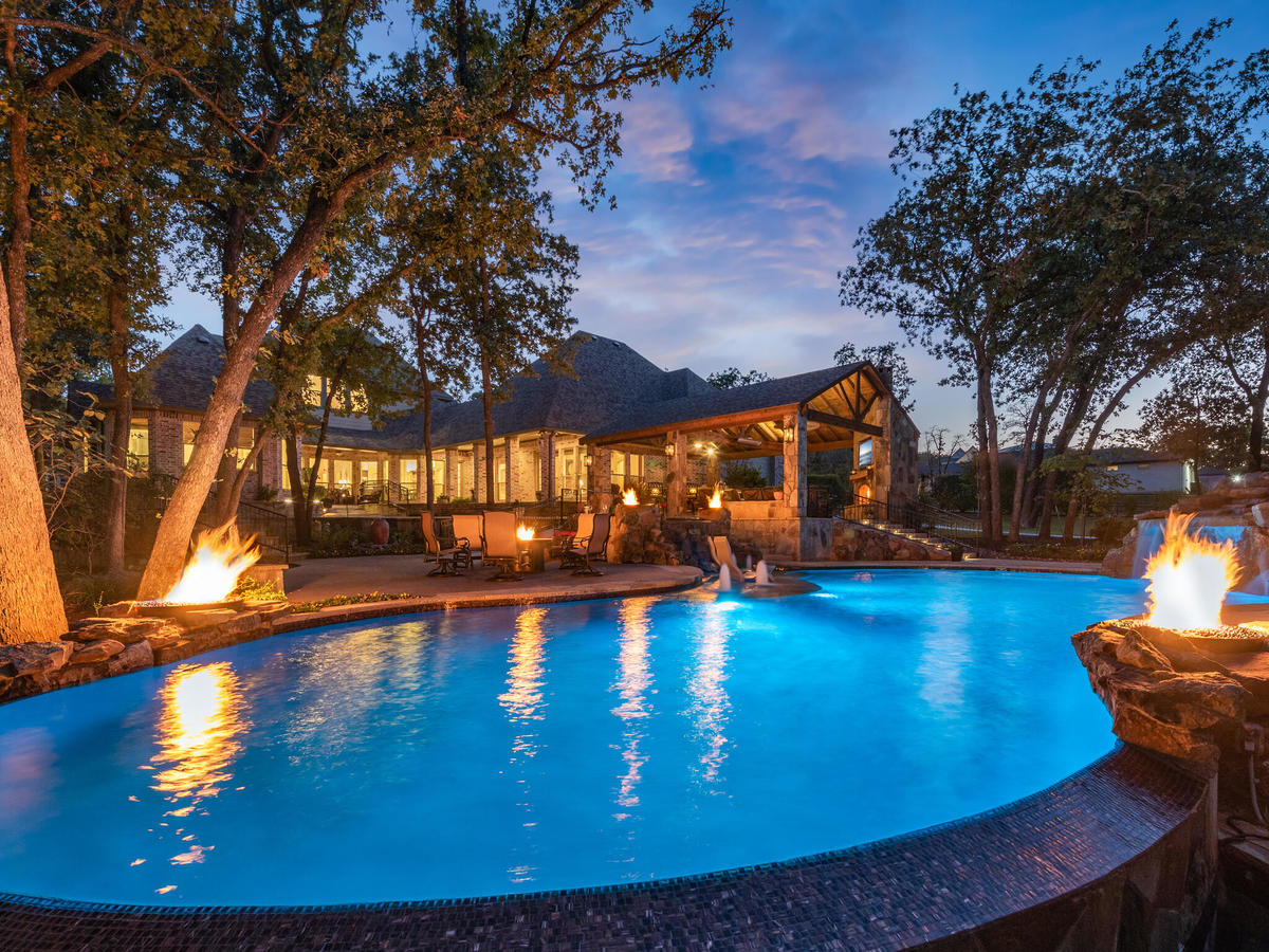 backyard pool surrounded by fire pits and patio